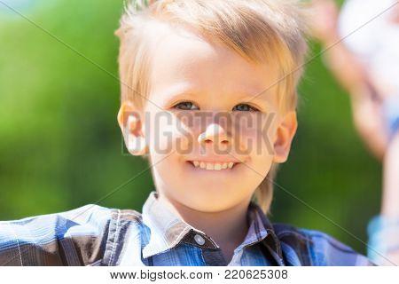 Closeup portrait of a smiling little boy outdoors