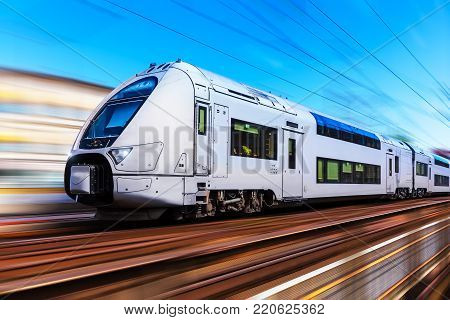 Scenic summer view of modern high speed passenger commuter train on tracks with motion blur effect