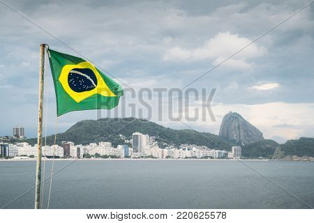 Brazilian flag on a pole waving set against Copacabana, Rio de Janeiro, Brazil background with the iconic Sugarloaf Mountain