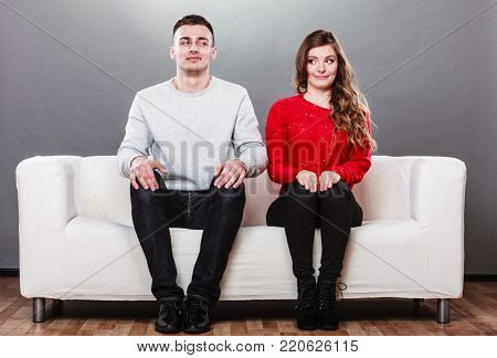 Shy woman and man sitting on sofa couch next each other. First date. Cute girl and handsome guy meeting dating and trying to talk.