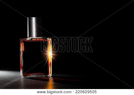 Luxury perfume bottle. Expensive fragrance in the spotlight. Self indulgent decadence and the pleasure of excess. Amber cologne highlighted against black background with copy space.