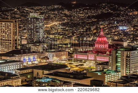 SAN FRANCISCO, CALIFORNIA, USA - OCTOBER 27, 2017: City Hall at night illuminated with red and white projectors. Construction was completed in 1915.