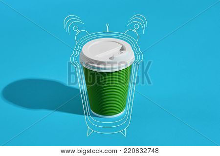 Hot coffee in green paper cup with white lid on blue background with shadow, blurred and soft focus image. Still life. Copy space. Wake up Painted alarm clock