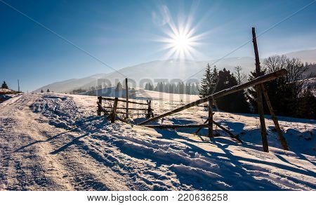 wooden fence on snowy meadow. lovely rural scenery on a bright sunny day. location Pylypets, Ukraine