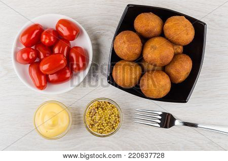 Small fried pies stuffed with meat in bowl, mustard, mayonnaise, tomatoes in saucer and fork on wooden table. Top view