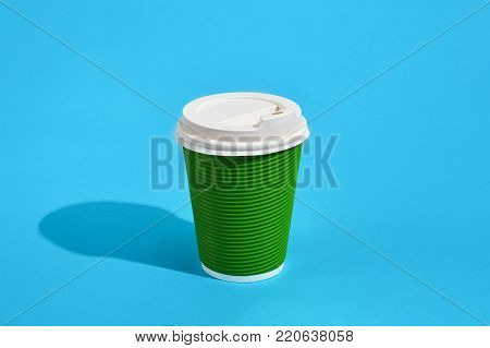 Hot coffee in green paper cup with white lid on blue background with shadow, blurred and soft focus image. Still life. Copy space