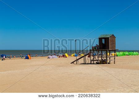 MAR DE LAS PAMPAS, BUENOS AIRES, ARGENTINA - DECEMBER 26, 2017: The people enjoying the beach in a sunny day of summer. The lifeguard tower in foreground.