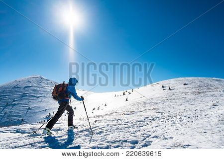 Skialpinist on snowy mountains, Tourist on trip in snowy mountains, Background winter sport, Winter sport for one, Symbol of winter tourism, Winter mountains advertising, hiker sporting in winter