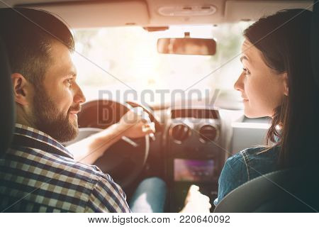 Careful driving. Beautiful young couple sitting on the front passenger seats and smiling while handsome man driving a car.