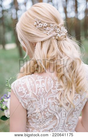 Portrait of lovely young bride with beautiful blond hair and curled hairstyle turned away on green background. Hair accessory: tiara, crown, beads. Closeup view