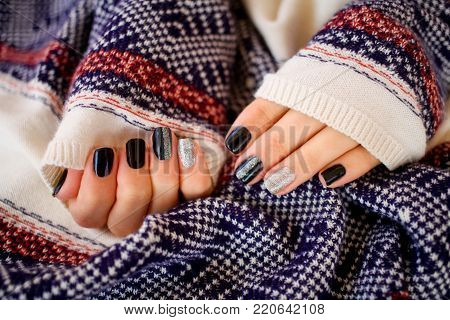 Beautiful hands with manicure in a knitted warm sweater.Manicure - Beauty treatment photo of nice manicured woman fingernails.