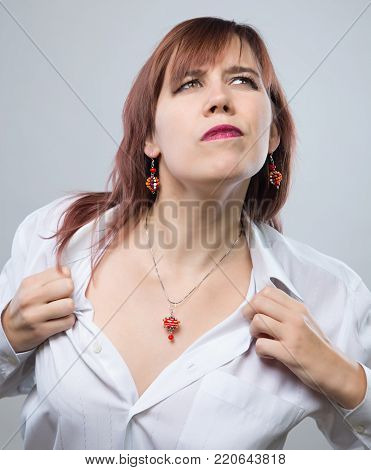 Young woman showing neckline on gray background