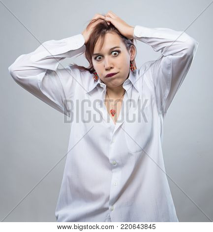 Portrait of young annoy woman on gray background