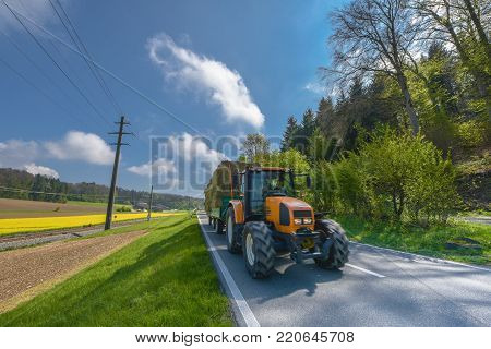 Swiss countryside - April 2017: tractor in the fields in Swiss countryside