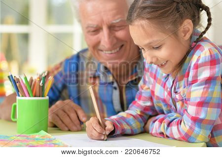 Portrait of happy Grandfather with granddaughter drawing together poster