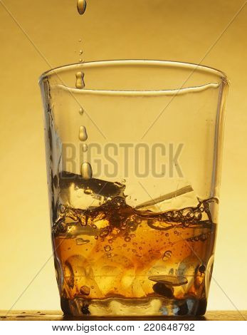 Transparent glass tumbler with ice cubes. In a glass filled with drink. A trickle of liquid. Photo on a yellow background. Still life.