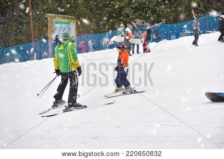 Skiing boy learning from ski teacher, in ski suit and helmet on ski resort