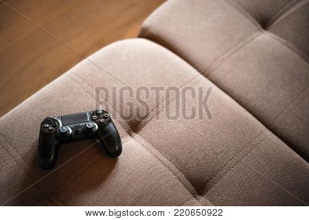 Black game joystick on a brown cozy corduroy couch. Computer game competition. Gaming concept.