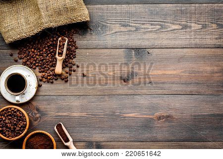 Coffee concept. Roasted beans, ground coffee, cup of espresso on dark wooden background top view.