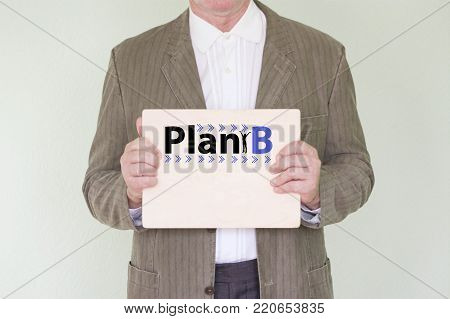 plan b concept. Silhouette of a girl. the man is a businessman in a jacket. business planning. holds a wooden nameplate