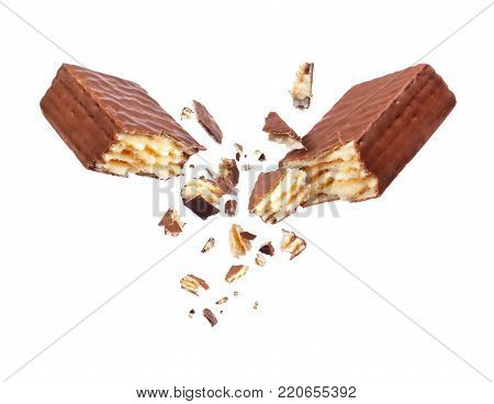 Chocolate waffle broken into two parts close up, isolated on white background
