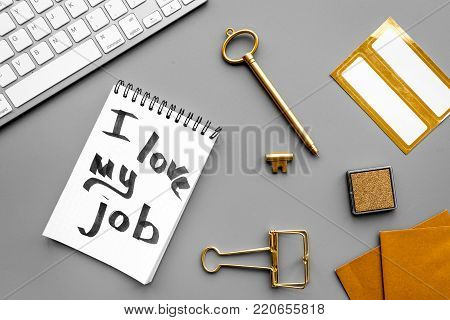 Find dream job. Handwritten motto I love my job in notebook near stationery on grey background top view.