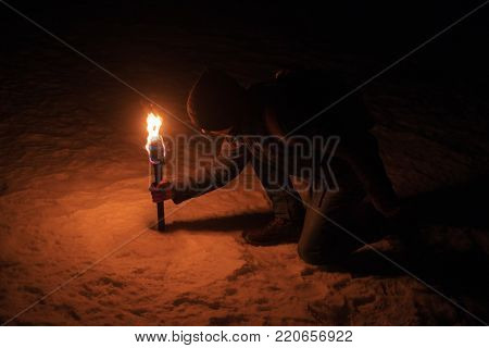 man holding burning flaming torch illuminating the cold winter night. lonely dark background mistical backdrop wallpaper