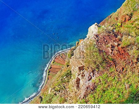 Look into the abyss on the high cliffs, the blue sea and the rocky beaches on the Portuguese island of Madeira