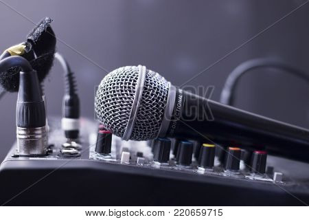 Closeup of microphone on mixing table audio equipment.