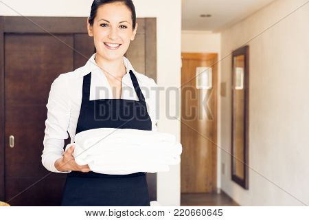 Young happy maid cleaning uo a hotel room