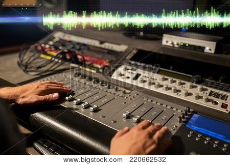 music, technology, people and equipment concept - sound engineer hands using mixing console at recording studio