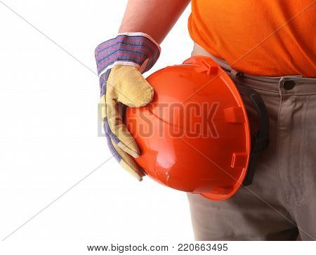 worker in protective gloves holds an orange hard hat in his hand. Safety helmet