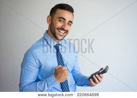 Closeup portrait of cheerful young handsome man looking at camera, pumping fist and holding calculator. Success concept. Isolated view on grey background.