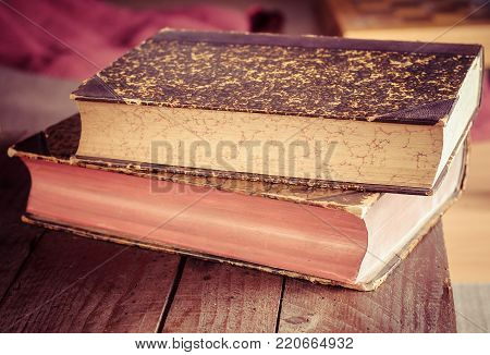 pile of old books on wooden brown table in bookstore
