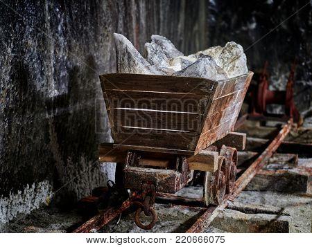 Old mine wagon with illuminated salt stones in Turda salt mine, Romania