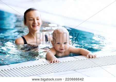 Mother teaching baby to swim. Portrait of a charming 11 months child in the classroom in a swimming pool. Healthy Family Life.