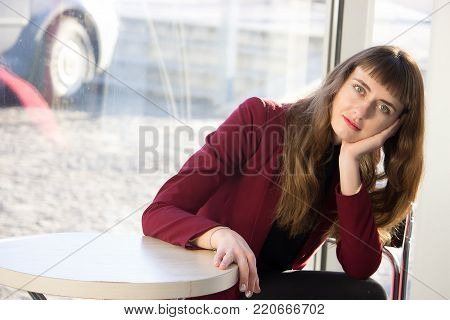 Young bored girl sitting waiting for coffee and for her boyfriend at cafe. Speed dating, unsuccessful meeting