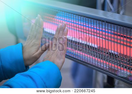 A woman in a blue jacket warmes her palms near an electric heater