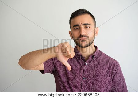 Closeup portrait of disappointed young handsome man looking at camera and showing thumb down. Disapproval concept. Isolated front view on grey background.