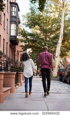Rear View Of Couple Walking Along Urban Street In New York City