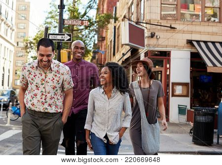 Group Of Friends Crossing Urban Street In New York City