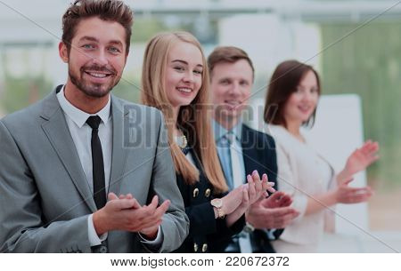 Business colleagues looking at camera and applauding in the offi