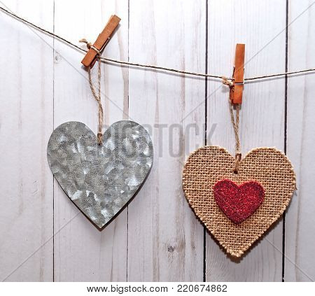 Two hearts, one silver and the other one brown with a smaller red heart in it's center, hanging on a line in front of a white washed fence