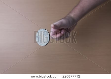 Concept image of flipping a coin. A conceptual image of flipping a Canadian silver coin up in the air.