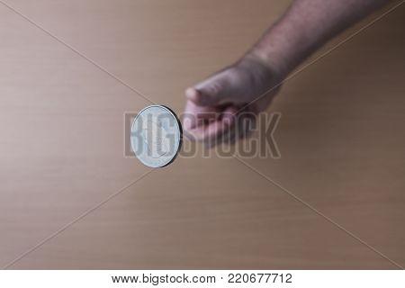 Concept image of flipping a coin. A conceptual image of flipping a Canadian silver coin up in the air.