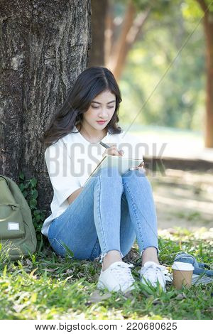 Asian Woman Sketch Picture On Book With Attractive Smiling At Garden. People Lifestyle Concept.
