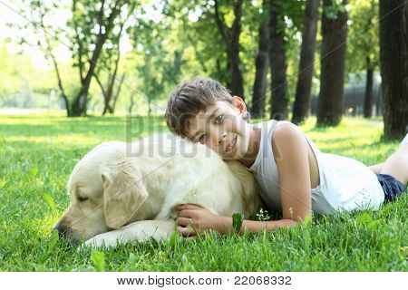 Little boy in the park with a golden retriever dog poster
