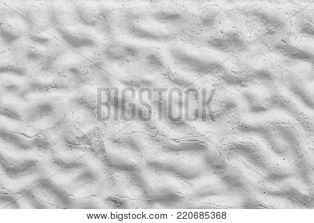White decorative colored surface as seamless texture or a background with wavy irregular pattern .