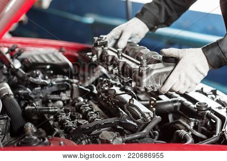 Repairing of modern diesel engine, workers hands and tool. Car mechanic looking at engine for analysis symptoms of car at maintenance repair service station.
