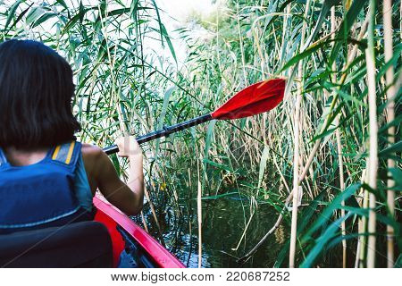 girl in the kayak swims through the jungle. a trip across the river through the jungle and thickets of grass.